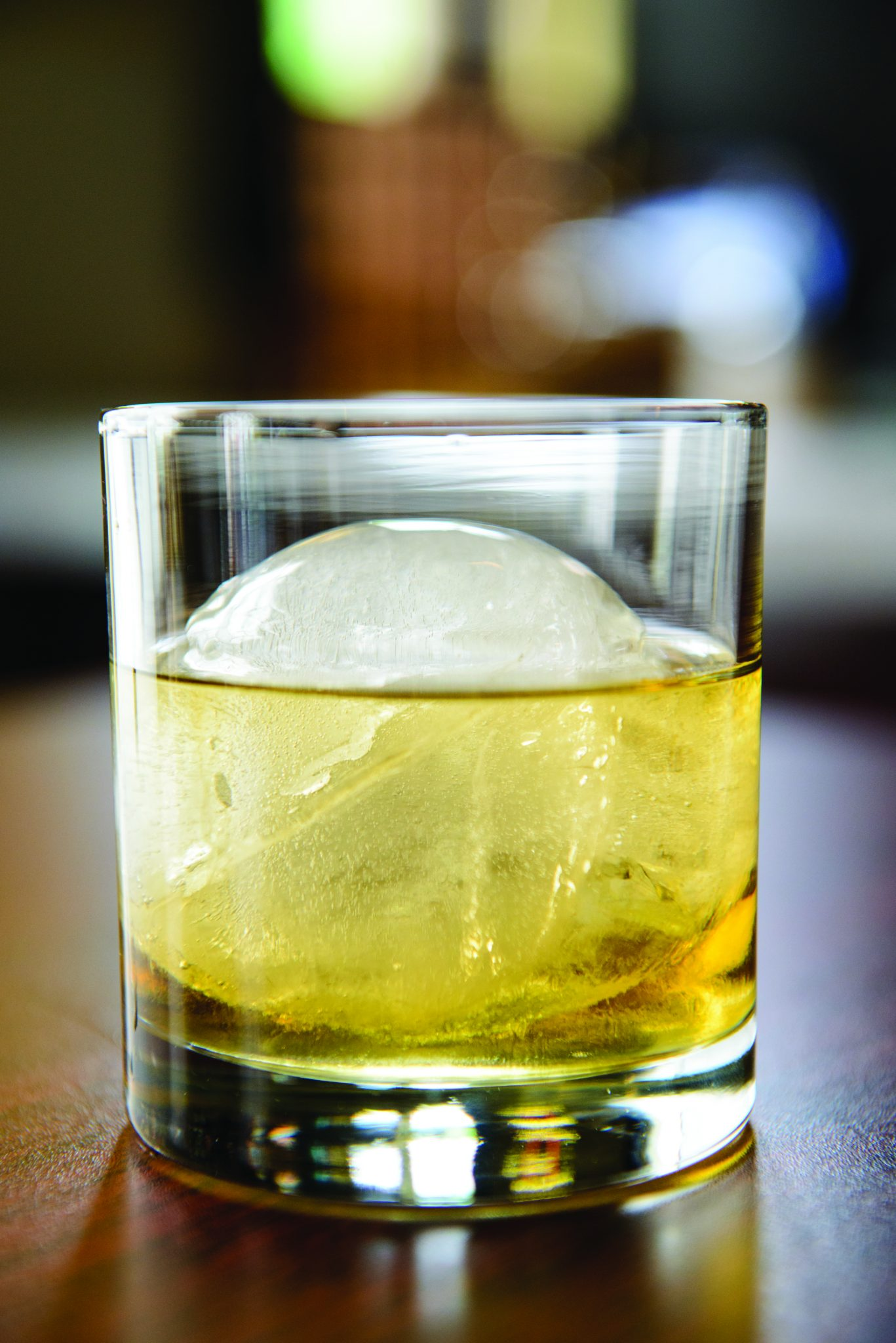 Whiskey in a glass tumbler with a large ice ball